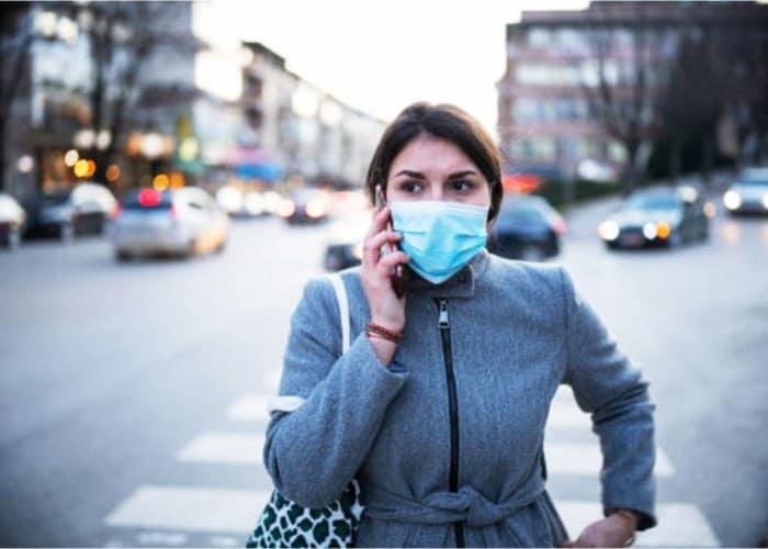 mujer con mascarilla llamando por telefono